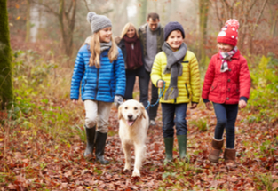 family walking through the woods during fall with winter jackets on and a dog